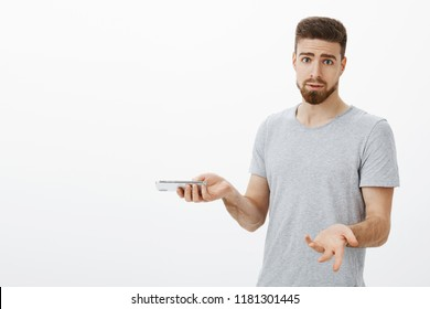 Why keep annoying me I am talking on phone. Confused and bothered silly masculine man with beard and blue eyes shrugging with raised palms holding smartphone, interrupted during important conversation