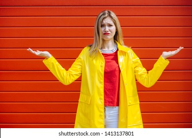 Why me. Portrait of confused and clueless clumsy blond woman in yellow coat shrugging with hands spread sideways standing questioned and sily over red background, unaware