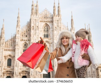 Why not to hang out in Italian fashion capital Milan on winter holidays with family. Mother with shopping bags pointing on something to daughter while in front of Duomo