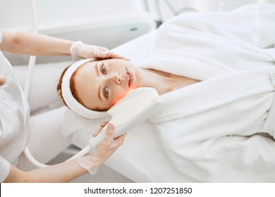 Why not pamper yourself with facial or body treatment. red haired woman with pefect freckled skin getting skin rejuvenation with RF lifting apparatus at at professional beauty salon, top view