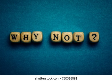 Why Not question - letters on wooden cubes on dark blue background with vignette, motivation and inspiration concept
