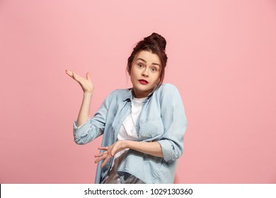 Why is that. Beautiful female half-length front portrait isolated on pink studio backgroud. Young emotional surprised and bewildered woman. Human emotions, facial expression concept. Trendy colors.