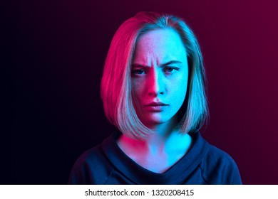 Why is that. Beautiful female half-length portrait isolated on trendy neon studio backgroud. Young emotional surprised, frustrated and bewildered woman. Human emotions, facial expression concept.
