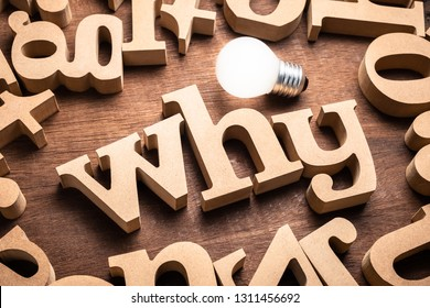 WHY word in scattered wood letters on the table with glowing light bulb