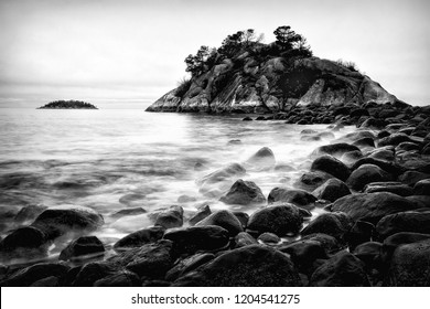 Whyte Islet Tide. Time lapse view of waves crashing onto the wet rocks of a rugged seashore near Vancouver, British Columbia, Canada. Black and white seascape background with copy space. Vintage look.