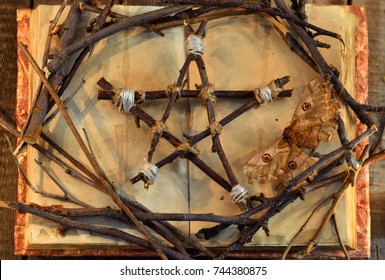 Wicca pentagram, moth - death symbol, and tree branches on open book with shabby pages in candle light, top view. Occult, esoteric, divination and wicca concept. Halloween vintage background