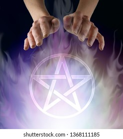Wiccan Pentacle Ceremony - witch's hands hovering above a transparent Pentacle symbol floating in smokey ethereal atmosphere  against a black background with copy space