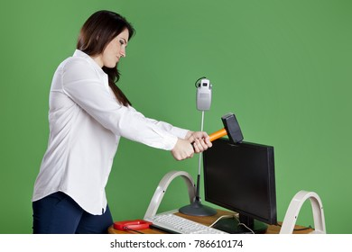Wicked businesswoman with hammer in hands breaks old computer. Woman crashed LCD monitor. Isolated on green background