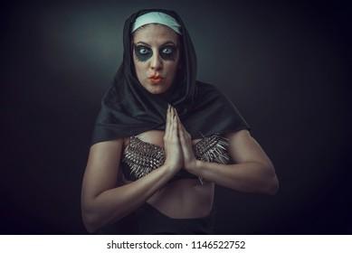 Wicked demon possessed nun praying to dark forces, devils or demons, surrendering to evil