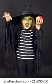 Wicked witch offering poisoned apple, kid in Halloween costume
