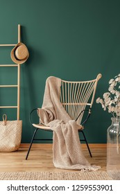 Wicker armchair with beige blanket and wooden ladder with wicker hat, real photo with copy space on empty green wall