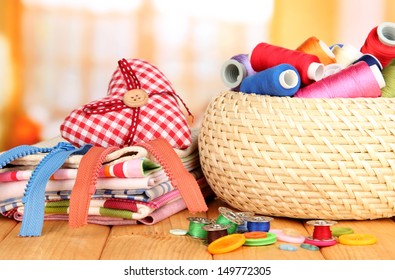 Wicker basket with accessories for needlework on wooden table, on bright background