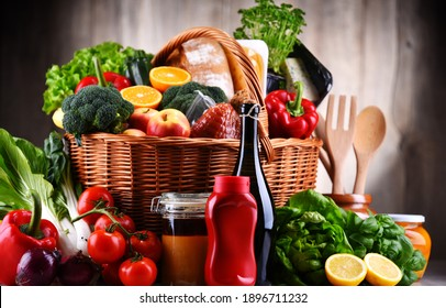 Wicker basket with assorted grocery products including fresh vegetables and fruits