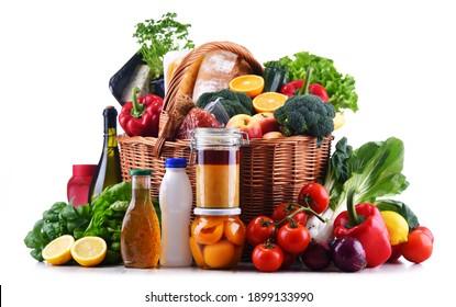 Panier en osier avec produits d'épicerie variés, y compris les légumes et les fruits frais