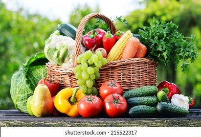 Wicker basket with assorted raw organic vegetables in the garden.