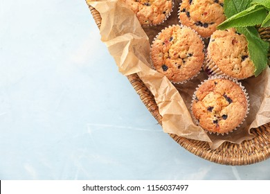 Wicker basket with blueberry muffins on table