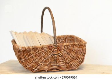 Wicker basket with books inside on a wooden table