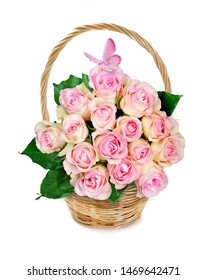 Wicker basket with bouquet of pink rose flowers and pink butterfly isolated on a white background