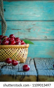 Wicker basket bowl, full of fresh picked cherry on a old rustic wooden table.
