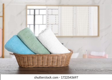 Wicker basket with clean soft towels on wooden table in bathroom. Space for text