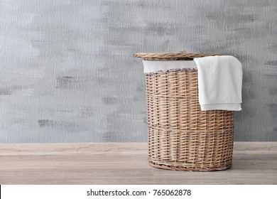 Wicker basket with dirty laundry on floor against grey wall