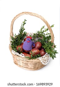 Wicker basket with easter eggs and decorations shot on white