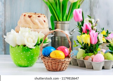 Wicker basket with Easter eggs on the table. Floral decorations in the background.