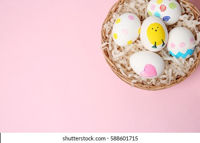 Wicker basket with Easter eggs on color background