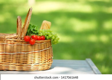 Wicker basket with food on table in park, space for text. Summer picnic