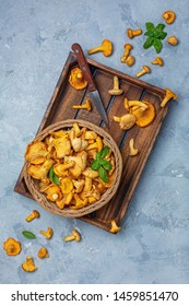 Wicker basket with forest chanterelles and a knife in a wooden box on a gray textured background. Top view.