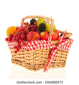 Wicker basket with fresh summer fruit isolated over white background