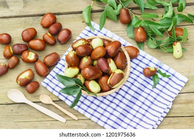 Wicker basket with fruits Ziziphus real, capiente, jujube, Chinese date, capiinit, jojoba, Chinese-date (lat.Ziziphus jujuba) and wooden spoons on a napkin. Harvest