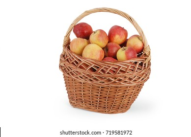 Wicker basket full of red and yellow apples isolated on white background with soft shadow