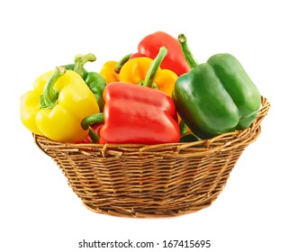 Wicker basket full of sweet green, yellow and red bell peppers isolated over white background