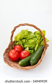 Wicker basket with green salad, tomatoes and cucumbers for a salad