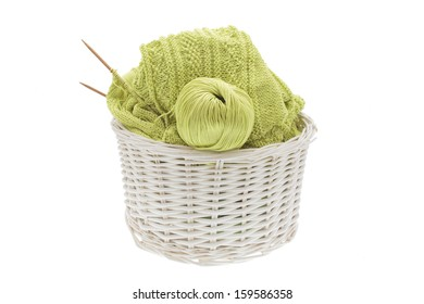 wicker basket of knitted cotton fabric, bamboo needles and yarn on a white background
