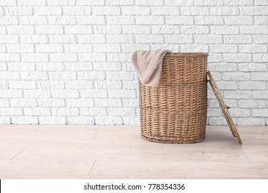 Wicker basket with laundry on floor against brick wall