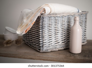 Wicker Basket with Linen, artistically arranged on a shelf with old milk bottle, and teasel plant