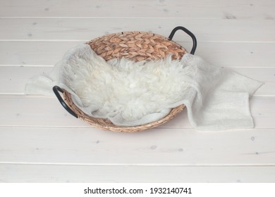 Wicker basket on a wooden background. Photo zone for taking pictures of a newborn baby. White fur, winding. Preparing for a photo session. Photoshoot. Props. Newborn nest.