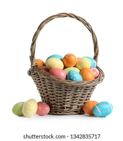Wicker basket with painted Easter eggs on white background