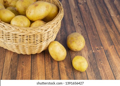 A wicker basket with potatoes on a wooden table