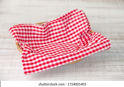Wicker basket with a red checked fabric napkin on a wooden white table