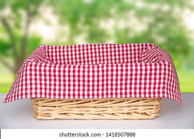 Wicker basket with a red cloth inside on a white table