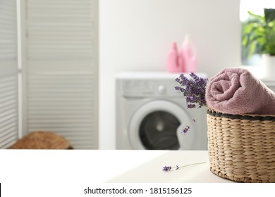 Wicker basket with rolled clean towel and lavender flowers on white table indoors. Space for text