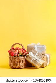 Wicker basket with roses and beautifully wrapped gifts on yellow background.