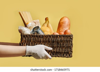 Wicker basket with a set of products in the hands in protective gloves isolated on a yellow background. Donation food concept.