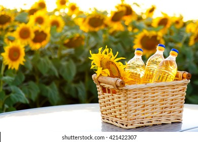 Wicker basket with sunflower and three bottles of oil on the background of the field