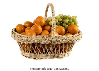 wicker basket with tangerines and grapes on a white background