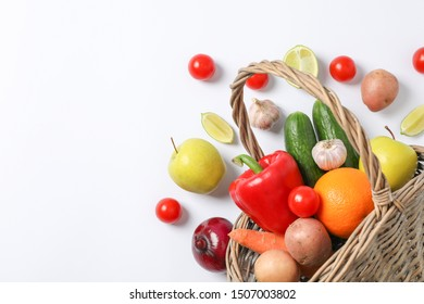 Wicker basket, vegetables and fruits on white background, space for text