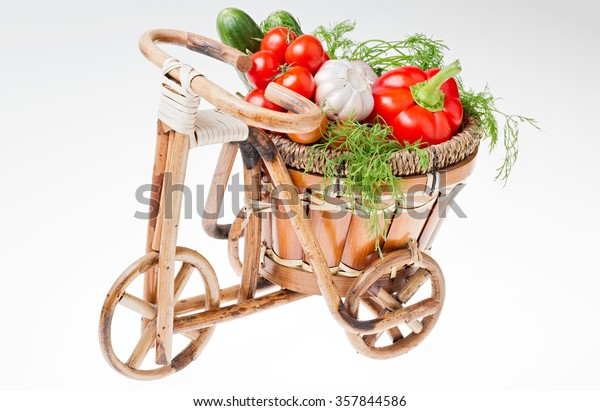 Wicker basket with vegetables : tomatoes, garlic, pepper, cucumber, dill  in the form of a Bicycle is harvest. Organic food. healthy Eating. The picture was taken on a white background.